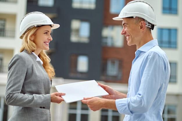 Supervisor entregando a documentação do prédio para um trabalhador feliz