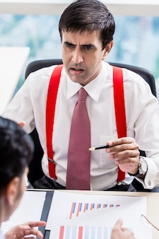 Supervisor fala para profissional subordinado em prédio de escritórios