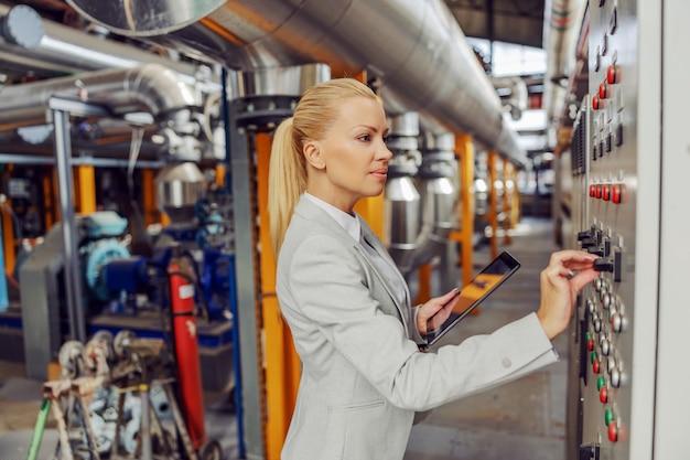 Supervisor loiro feminino em pé na planta de aquecimento ao lado do painel, ajustando as configurações e segurando o tablet.