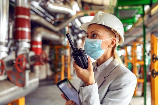 Supervisor mulher trabalhadora com máscara facial e capacete segurando um tablet e falando por walkie talkie