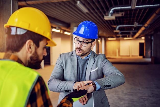 Supervisor nervoso sério discutindo com seu trabalhador e apontando para o relógio de pulso. o trabalho deve ser feito a tempo, sem desculpas. edifício no interior do processo de construção.
