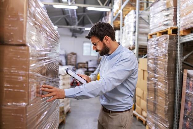 Supervisor no armazém ao lado das caixas e usando o tablet para verificar as mercadorias.