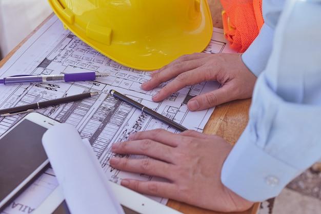 Supervisor que verifica na planta no local da construção civil