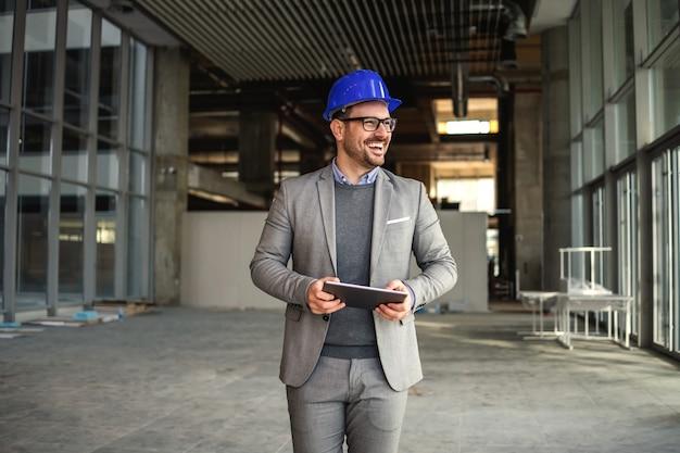 Supervisor sorridente andando no edifício em processo de construção com o tablet nas mãos e verificando as obras