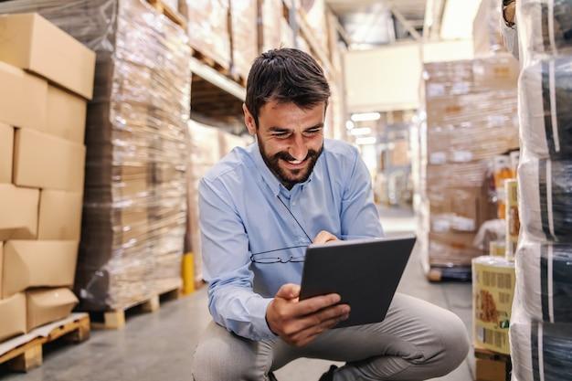 Supervisor sorridente barbudo jovem agachado no armazém e usando o tablet para verificar as mercadorias.