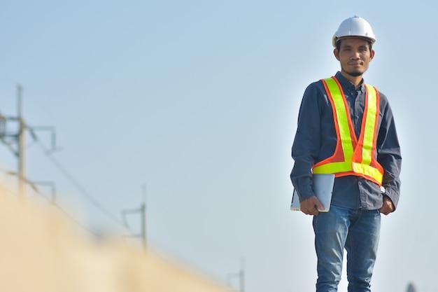Supervisor trabalhador da construção civil controle no canteiro de obras e pôr do sol de fundo