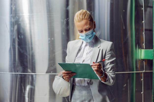 Supervisora dedicada, bem-sucedida, loira, mulher em trajes formais com máscara protetora, preenchendo a documentação enquanto estava na usina durante o coronavírus.