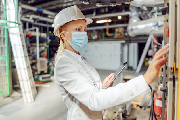 Supervisora loira dedicada com máscara facial em pé na estação de aquecimento ao lado do painel