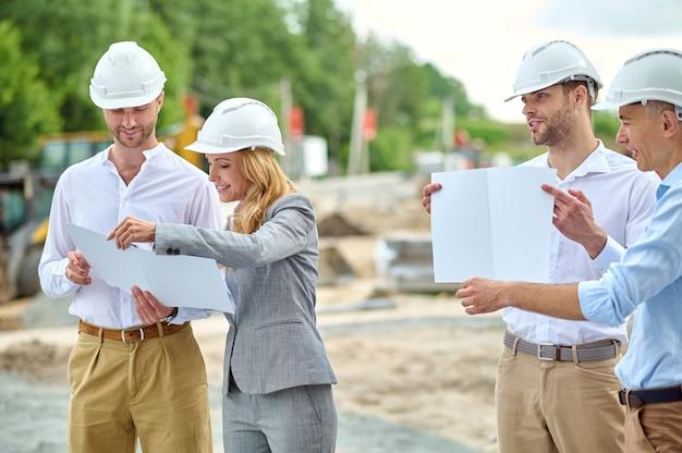 Supervisora sorridente e atraente em um capacete de segurança verificando os documentos do prédio na presença de construtores masculinos satisfeitos