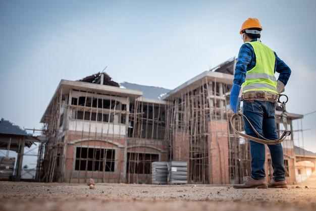 Supervisores ou contratados asiáticos estão assistindo a construção de grandes casas ou locais de trabalho em andamento.