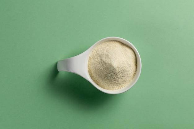 Suplemento de musculação em pó de proteína de soro de leite. vista superior da colher branca da porcelana com pó do sabor da baunilha. cor sólida: verde