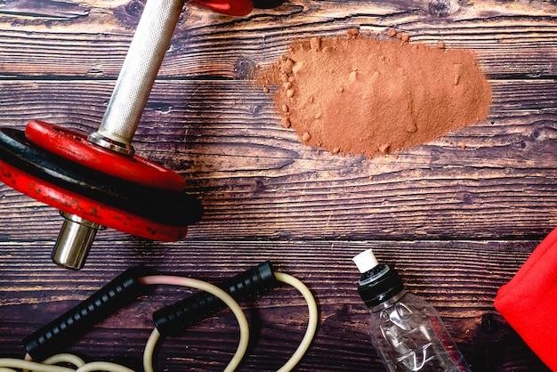 Suplemento de soro de proteína de cacau em pó no chão de uma academia durante um treino.