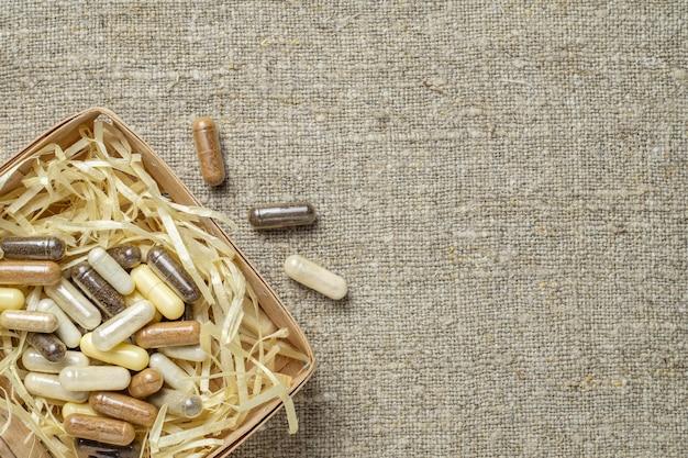 Suplementos dietéticos orgânicos à base de ervas e minerais em cápsulas em caixa de madeira em forma de ninho