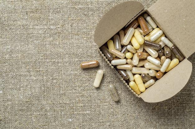 Suplementos dietéticos orgânicos à base de ervas e minerais em cápsulas em uma caixa de papelão