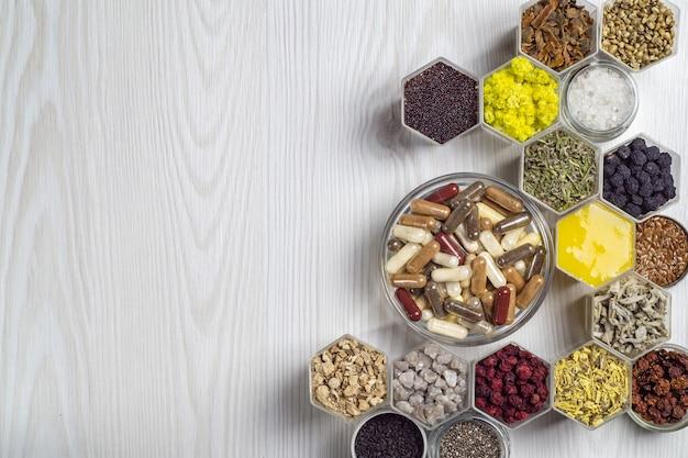 Suplementos dietéticos orgânicos à base de ervas e minerais em cápsulas. ingredientes para suplementos alimentares em potes hexagonais têm a forma de um favo de mel