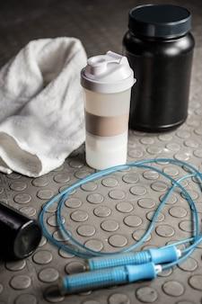 Suplementos e corda no chão no ginásio crossfit
