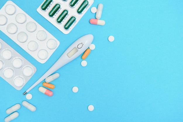Suplementos e embalagens de comprimidos, close-up. lugar para inserir seu texto, fundo azul. farmacêuticos e clínicas.