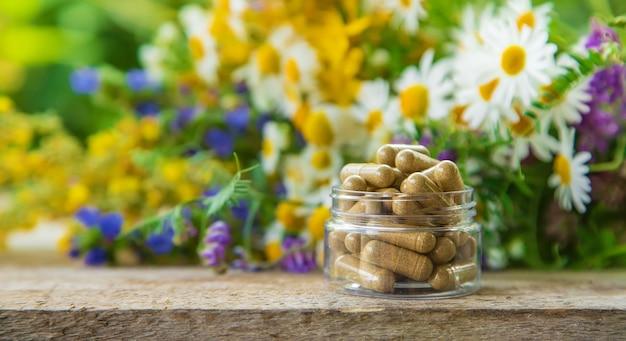 Suplementos e vitaminas com ervas medicinais em uma mesa de madeira com fundo de vegetação turva