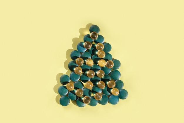 Suplementos e vitaminas em forma de árvore de natal em fundo amarelo, copie o espaço.