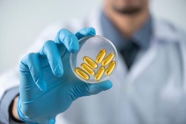 Suplementos nutricionais óleo de fígado de bacalhau omega-3 vitamina d, um óleo de peixe cápsulas, óleo de cápsula na mão pesquisador