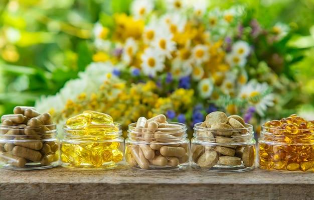 Suplementos, vitaminas e ervas medicinais em potes de vidro na mesa de madeira no fundo de flores desfocadas