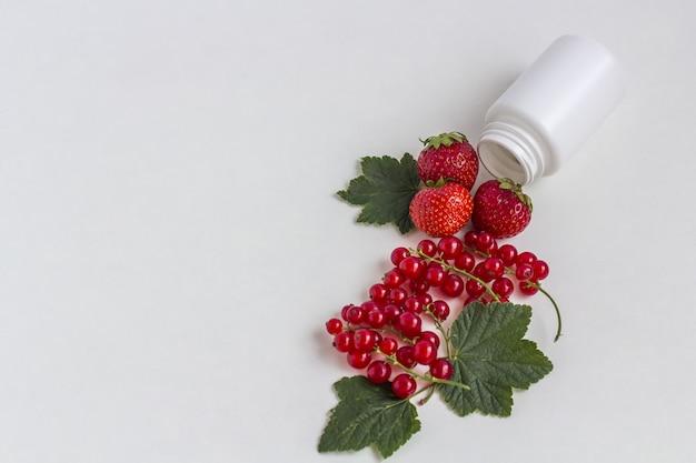 Suplementos vitamínicos como uma cápsula com frutas frescas do frasco de medicamento branco.