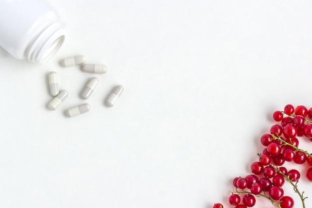Suplementos vitamínicos como uma cápsula com frutas frescas do frasco de medicamento.