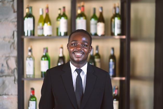 Suporte africano do homem de negócio e sorriso com a garrafa do champanhe para o fundo.