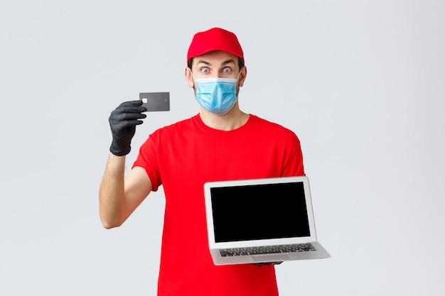 Suporte ao cliente, pacotes de entrega covid-19, conceito de processamento de pedidos online. correio animado e surpreso com uniforme vermelho, máscara e luvas, mostrando cartão de crédito para pagamento de pedidos e laptop