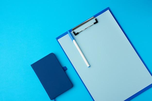 Suporte azul com folhas vazias e caderno sobre um fundo azul