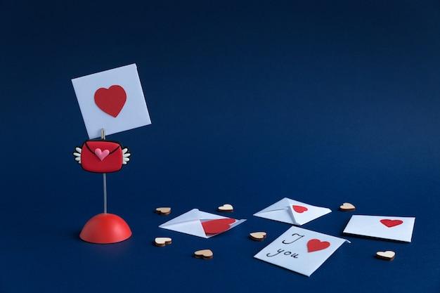 Suporte com dia dos namorados, envelopes com mensagens e pequenos corações de madeira, sobre fundo de papel azul escuro com lugar para texto.