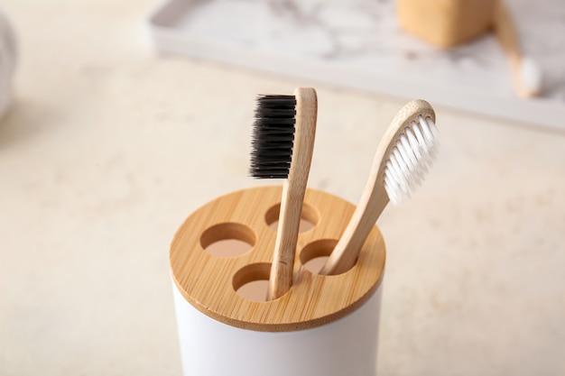 Suporte com escovas de dente de madeira na mesa do banheiro