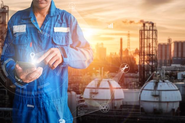 Suporte de engenheiro da ásia segurando o toque da mão do telefone inteligente na planta de refinaria de petróleo e gás