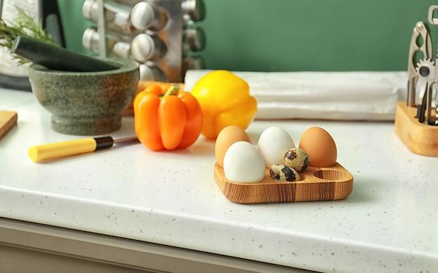 Suporte de madeira com ovos de galinha na mesa da cozinha