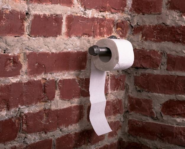 Suporte de metal para papel higiênico e rolo de papel toalha em estilo loft na parede de tijolos