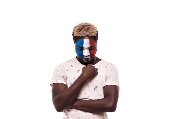 Suporte de torcedor perdedor chateado da seleção afro-francesa com o rosto pintado isolado no fundo branco