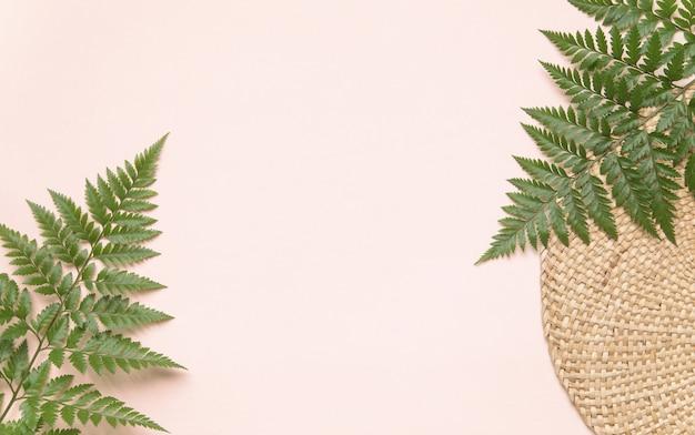 Suporte de vime redondo e folhas de palmeira na parede rosa. conceito de estilo flatlay eco com texto local