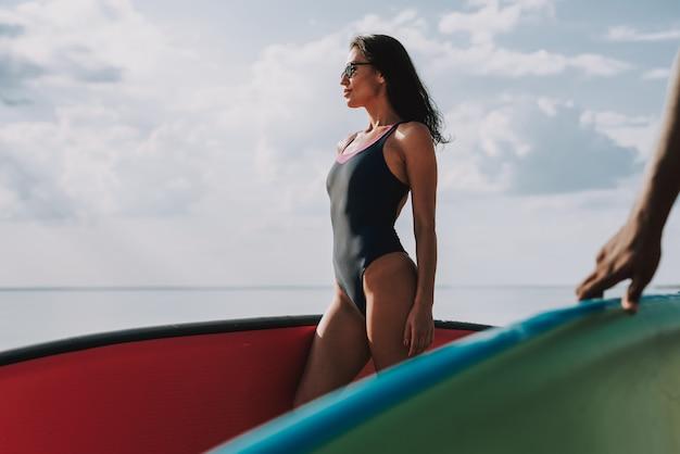 Suporte fêmea novo do surfista na praia com placa.