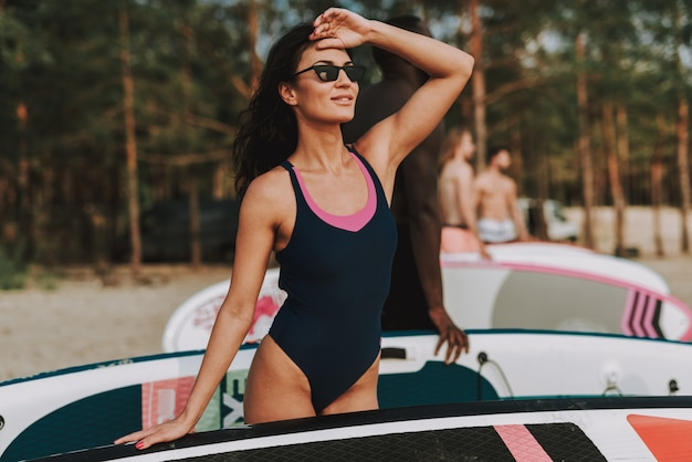 Suporte fêmea novo do surfista na praia no roupa de banho.