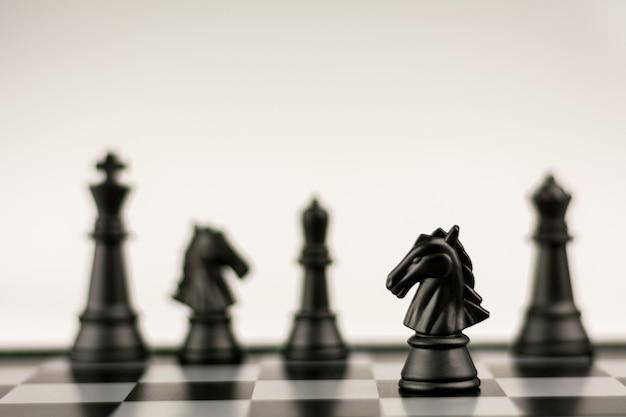 Suporte preto da xadrez do cavalo sozinho em um tabuleiro de xadrez. - vencedor de negócios e conceito de luta.