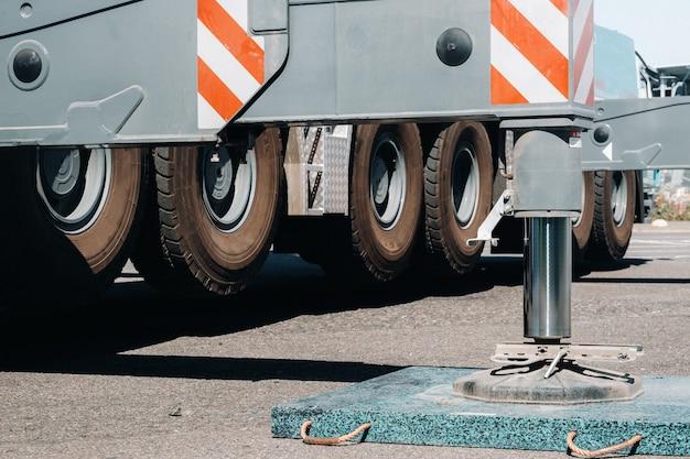 Suportes hidráulicos para as pernas do guindaste são instalados para estabilidade.