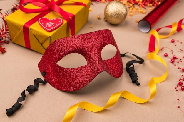 Suportes para o. presentes embalados em uma caixa de presente amarela embrulhada em fita vermelha, rolos de papel de embrulho, máscara de baile de máscaras vermelha e bolas de natal. fechar-se.