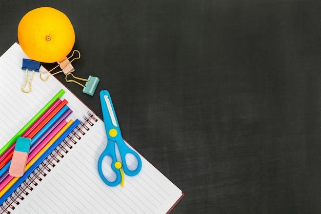 Suprimentos com notebook e laranja na lousa