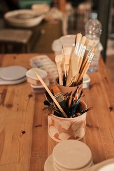 Suprimentos com pincéis e ferramentas em suporte de barro artesanal na mesa de madeira