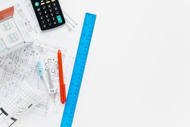 Suprimentos de arquitetura com calculadora na mesa branca
