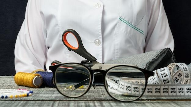 Suprimentos de costura e óculos para visão em uma mesa de madeira preta