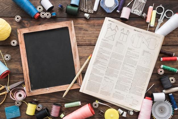 Suprimentos de costura e revista perto de quadro-negro