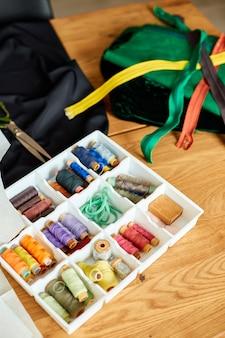 Suprimentos de costura em uma mesa de madeira: linha de costura, tesoura, pedaços de pano, agulhas, centímetros, padrão.