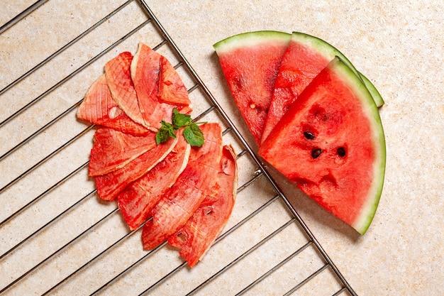 Suprimentos de inverno: fatias de melancia seca com pedaços frescos sobre fundo claro com grade.
