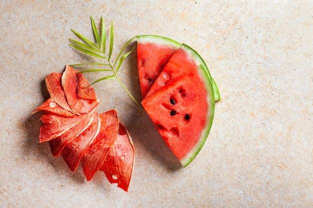 Suprimentos de inverno: fatias de melancia seca com pedaços frescos sobre fundo claro.